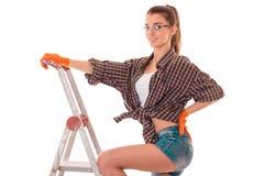 在制服的年轻深色的妇女建造者在看和摆在照相机的梯子做整修隔绝在白色 免版税库存图片