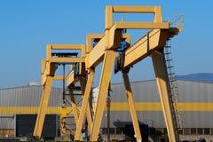 在制造业工厂的一个灰色和黄色大厦的前面桥式起重机 库存照片