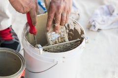 在刷子上的专业画家装货油漆从桶 免版税库存照片