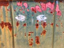 在削皮金属的钢印街道画眼睛 免版税库存照片