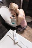 在前景和哀伤的病的妇女的妊娠试验坐她的在洗手间的膝盖在卫生间里 免版税库存照片
