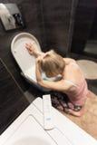 在前景和哀伤的病的妇女的妊娠试验坐她的在洗手间的膝盖在卫生间里 库存图片