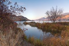 在前景和日落的镇静湖风景有秋叶的和草在遥远的山点燃 免版税库存照片