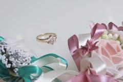 在前景婚礼钮扣眼上插的花 在他们后谎言一个金黄圆环 在一个空白背景 免版税库存照片