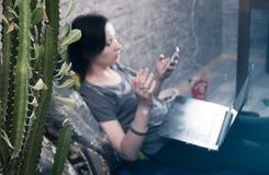 在前景的仙人掌, T恤杉的一个年轻深色的女孩和牛仔裤,选择聚焦, 免版税库存照片