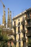 在前景的公寓有Sagrada Familia圣洁家庭教会看法由建筑师安东尼Gaudi,巴塞罗那,西班牙的在1882年开始的 库存图片