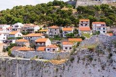 在前景的古老被破坏的墙壁和房子红色屋顶背景的 免版税库存图片