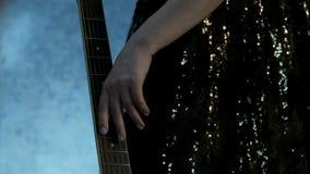 在前景的吉他fretboard 音乐会礼服的女孩过来和轻轻地通过她移交串 题材为 股票视频