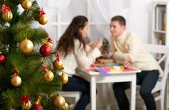 在前景的圣诞树与defocused浪漫年轻夫妇坐在桌、愉快的人民和爱概念,新年holida上 库存图片