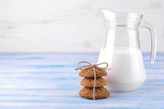 在前景的在一块玻璃的堆和牛奶堆的麦甜饼在一张蓝色木桌上 bacterias 美味 免版税库存图片