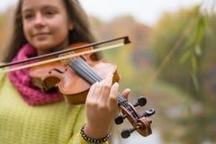 在前景的小提琴,女孩在秋天的弹小提琴 图库摄影