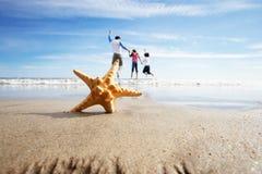 在前景的海星当与孩子的父亲戏剧在海 免版税图库摄影