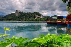 在前景的游船,流血的海岛在backgroun 免版税库存图片