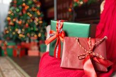 在前景的绿色和红色圣诞节礼物特写镜头 红色丝带弓 与被弄脏的光和树的抽象背景 库存照片
