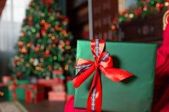 在前景的绿色圣诞节礼物特写镜头 红色丝带弓 与被弄脏的光和树的抽象背景 复制 库存图片