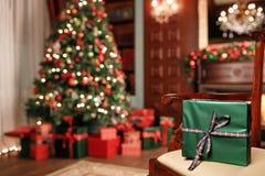 在前景的绿色圣诞节礼物特写镜头 红色丝带弓 与被弄脏的光和树的抽象背景 复制 免版税库存照片
