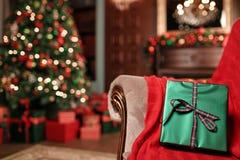 在前景的绿色圣诞节礼物特写镜头 红色丝带弓 与被弄脏的光和树的抽象背景 复制 图库摄影