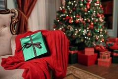 在前景的绿色圣诞节礼物特写镜头 红色丝带弓 与被弄脏的光和树的抽象背景 复制 免版税库存图片