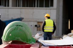 在前景的绿色安全安全帽 背景的建筑工人 图库摄影