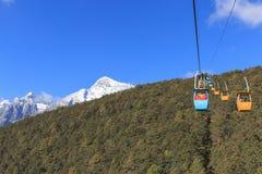在前景的缆车与里面有些的游人和玉龙雪山 免版税库存照片
