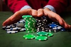 在前景的芯片,在弄脏拿着芯片的一个人的手,打扑克 库存图片