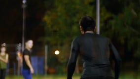 在前景,从后面的守门员打球,夜射击 股票录像