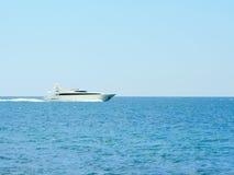 在前面充分开阔水域的白色速度yatch 库存照片
