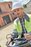 在前面建筑机械的司机在建筑工地 免版税库存图片