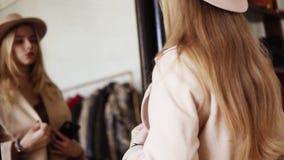 在前面的有吸引力的白肤金发的女孩身分在米黄外套和时髦帽子的镜子,做照片与她的神色 影视素材