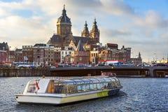 在前面的游船航行大教堂圣徒尼古拉斯在晚上阿姆斯特丹 免版税库存照片