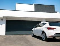 在前面的白色汽车有车库门的房子 免版税库存图片