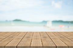 在前面的空的木桌有在海滩的被弄脏的背景 库存图片