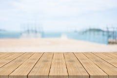 在前面的空的木桌有在海滩的被弄脏的背景 图库摄影