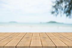 在前面的空的木桌有在海滩的被弄脏的背景 免版税库存图片