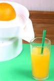 在剥削者、榨汁器和杯的桔子橙汁 免版税图库摄影