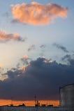 在剧烈的喜怒无常的日落的五颜六色的云彩在城市 库存照片