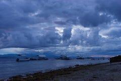 在剧烈的多云天空的风雨如磐的黑暗的日落在有渔和潜水木小船的热带海在石海岸线附近 库存图片