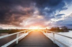 在剧烈的多云天空背景的美丽的木桥在五颜六色的日落的 免版税库存照片