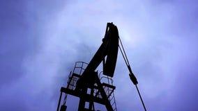 在剧烈的天空的小私有井架泵浦工作油有云彩背景 股票录像