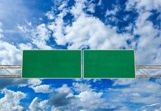 在剧烈的蓝天的空白的绿色路标与云彩 库存图片
