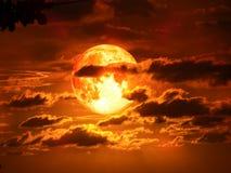 在剪影云彩的超级月亮在红色天空 库存图片