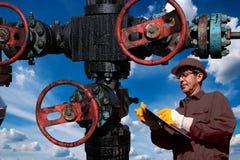 在剪贴板的工程师文字在反对多云天空蔚蓝的油井在背景中 免版税库存照片