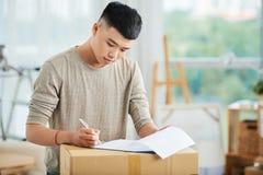 在剪贴板的年轻人文字在纸盒箱子 免版税库存照片