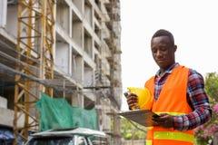 在剪贴板的年轻非洲黑人人建筑工人读书 库存照片