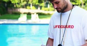 在剪贴板的微笑的救生员文字在游泳池边 影视素材
