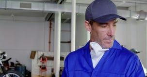 在剪贴板的男性技工文字在摩托车修理车库4k 股票录像