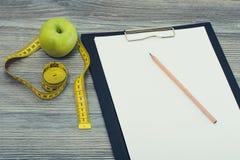 在剪贴板铅笔绿色鲜美新鲜的苹果和卷尺上顶上的看法照片冠上在木灰色背景在厨房ta 免版税库存照片