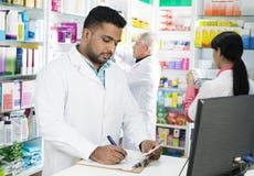 在剪贴板的化学家文字,当工作在Pharmac时的同事 免版税库存图片