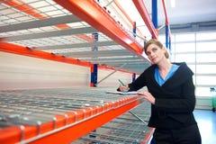 在剪贴板的女实业家文字在仓库里 免版税库存图片