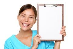 在剪贴板的愉快的女性Holding医生白纸 免版税库存照片